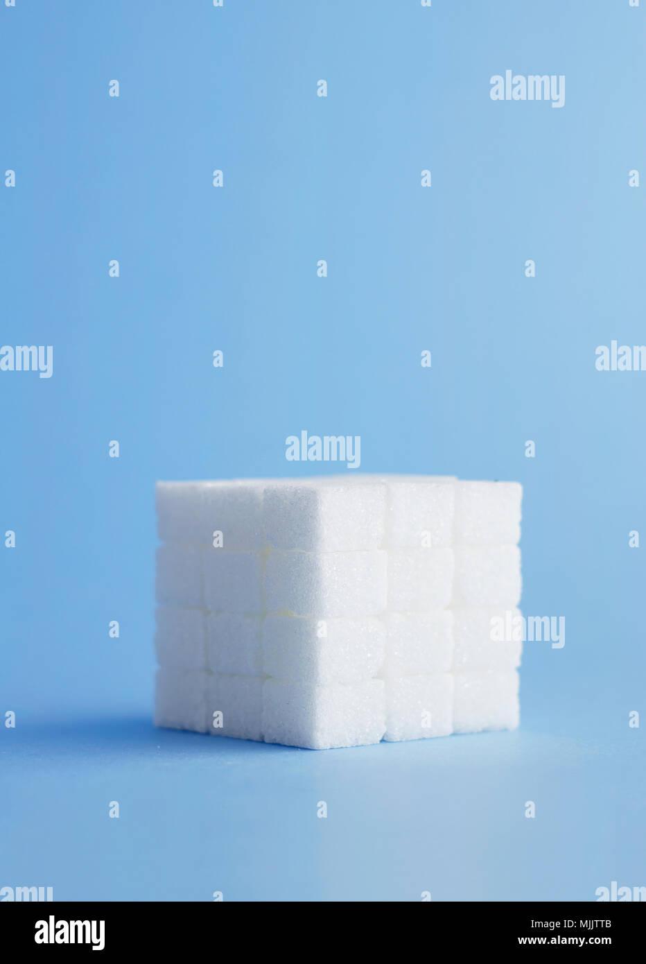 Cube fait de cubes de sucre sur fond bleu Photo Stock
