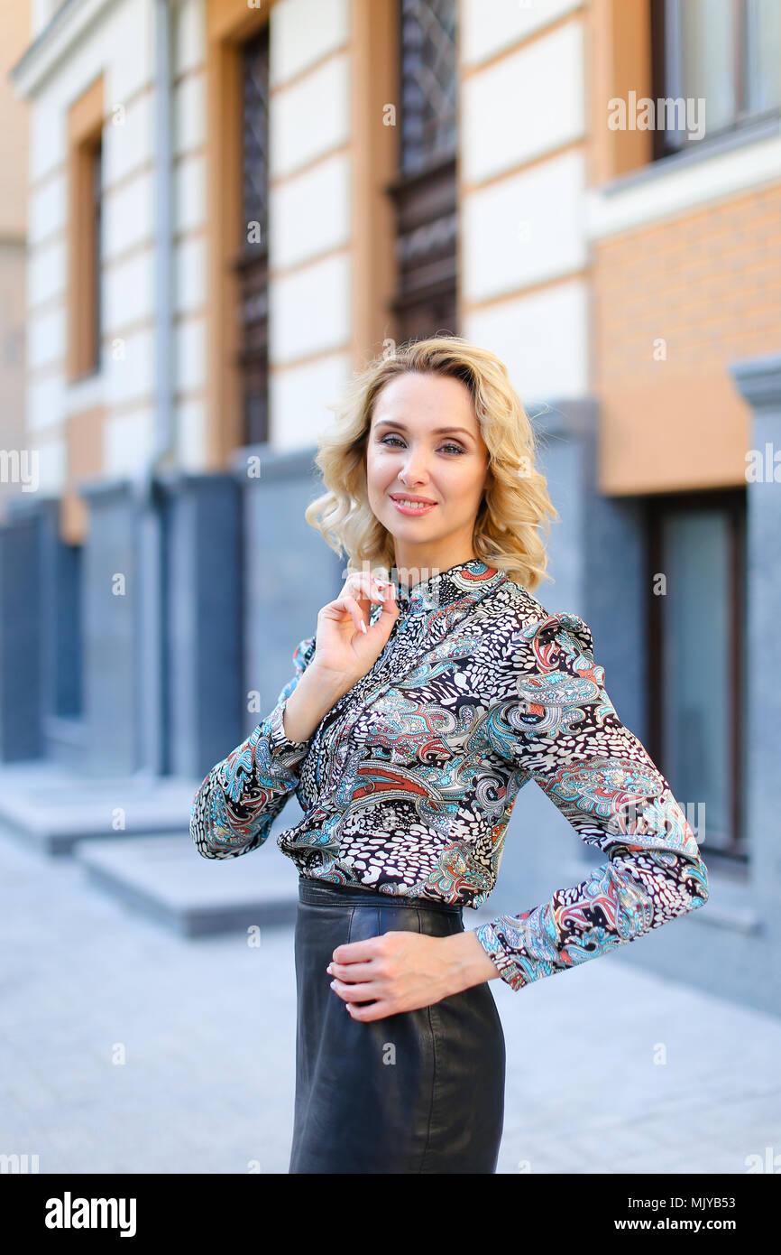 7afd668f807 Jeune femme portant jupe en cuir à l extérieur debout près du bâtiment.  Photo