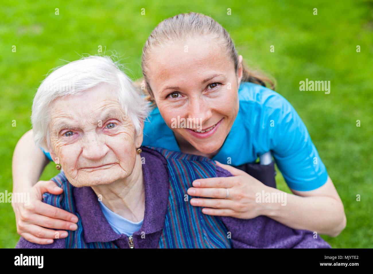 Portrait de personnes âgées handicapées femme assise dans un fauteuil roulant de passer du temps avec l'extérieur cheerful young caregiver Banque D'Images