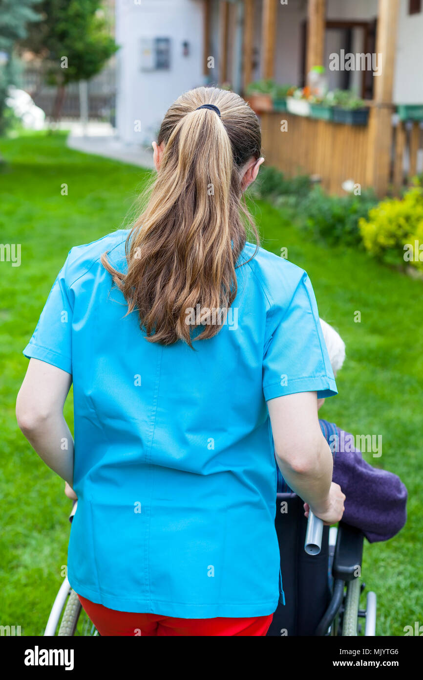 Les dépenses de soins en extérieur avec des handicapés senior woman, soins à domicile - vue arrière Banque D'Images