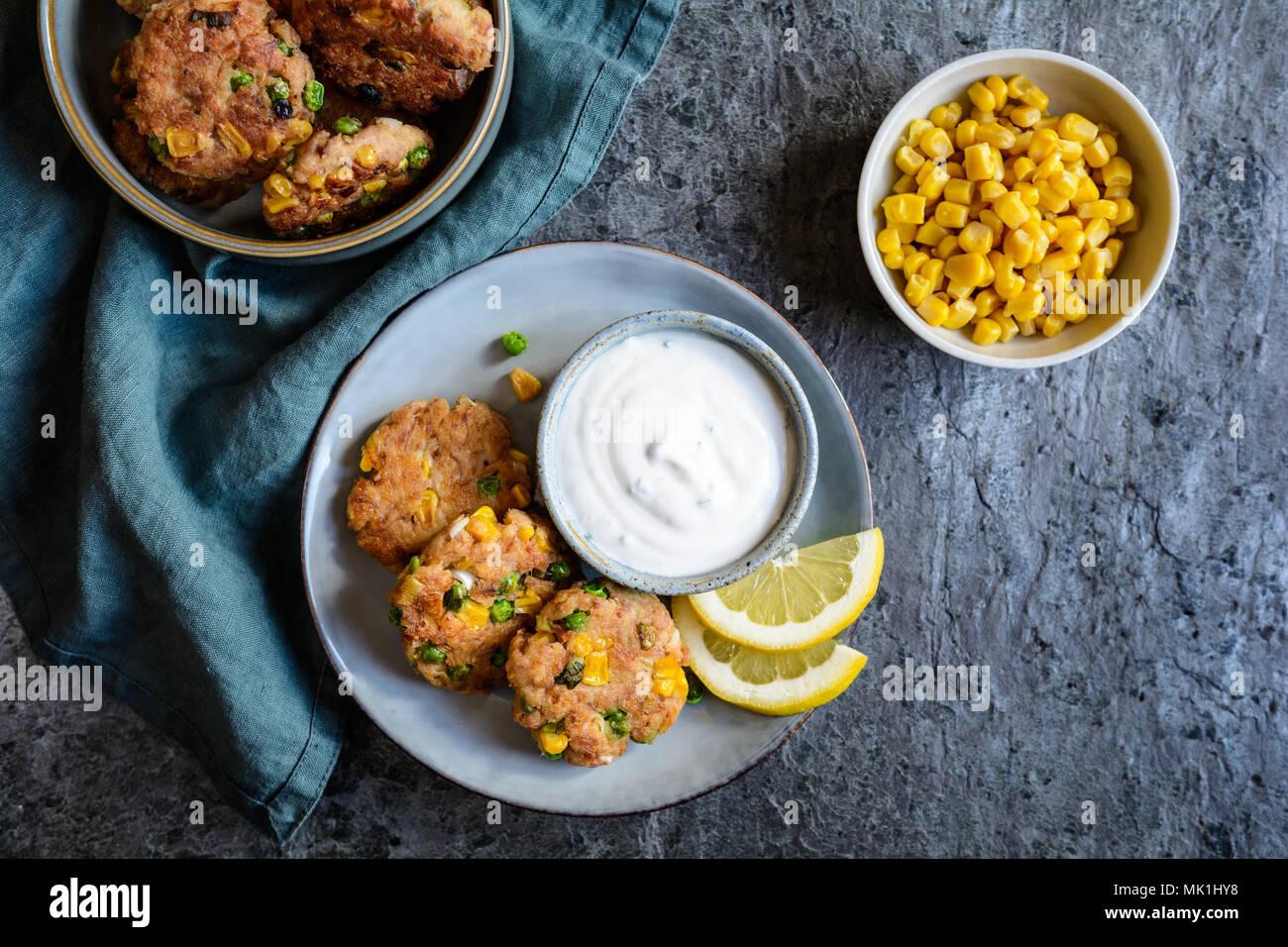 Thon saine cakes avec les pois verts, le maïs et l'échalote crème rafraîchir Photo Stock