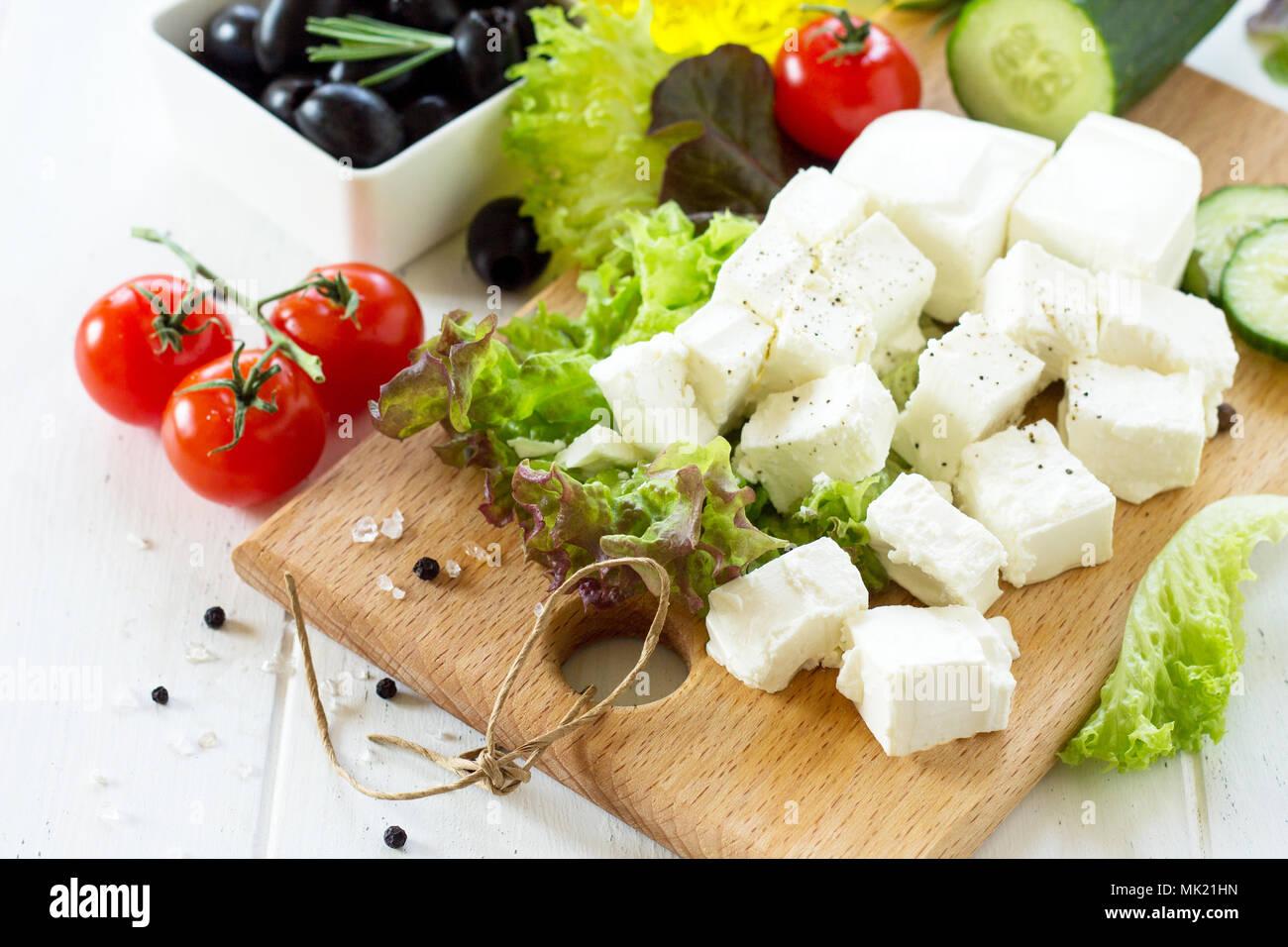 Feta et d'olives noires, de cuisine salade qreek avec légumes frais sur une table en bois blanc. Photo Stock