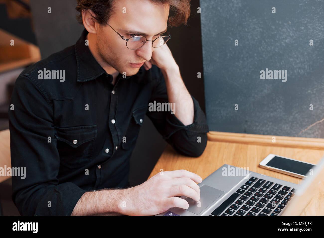 L'homme créatif designer travaillant sur son ordinateur portable lors de l'attente à l'ordre à son favori à l'intérieur, café étudiant travaillant sur le bénéfice net de bord pendant le petit déjeuner du matin au café de l'intérieur moderne Photo Stock