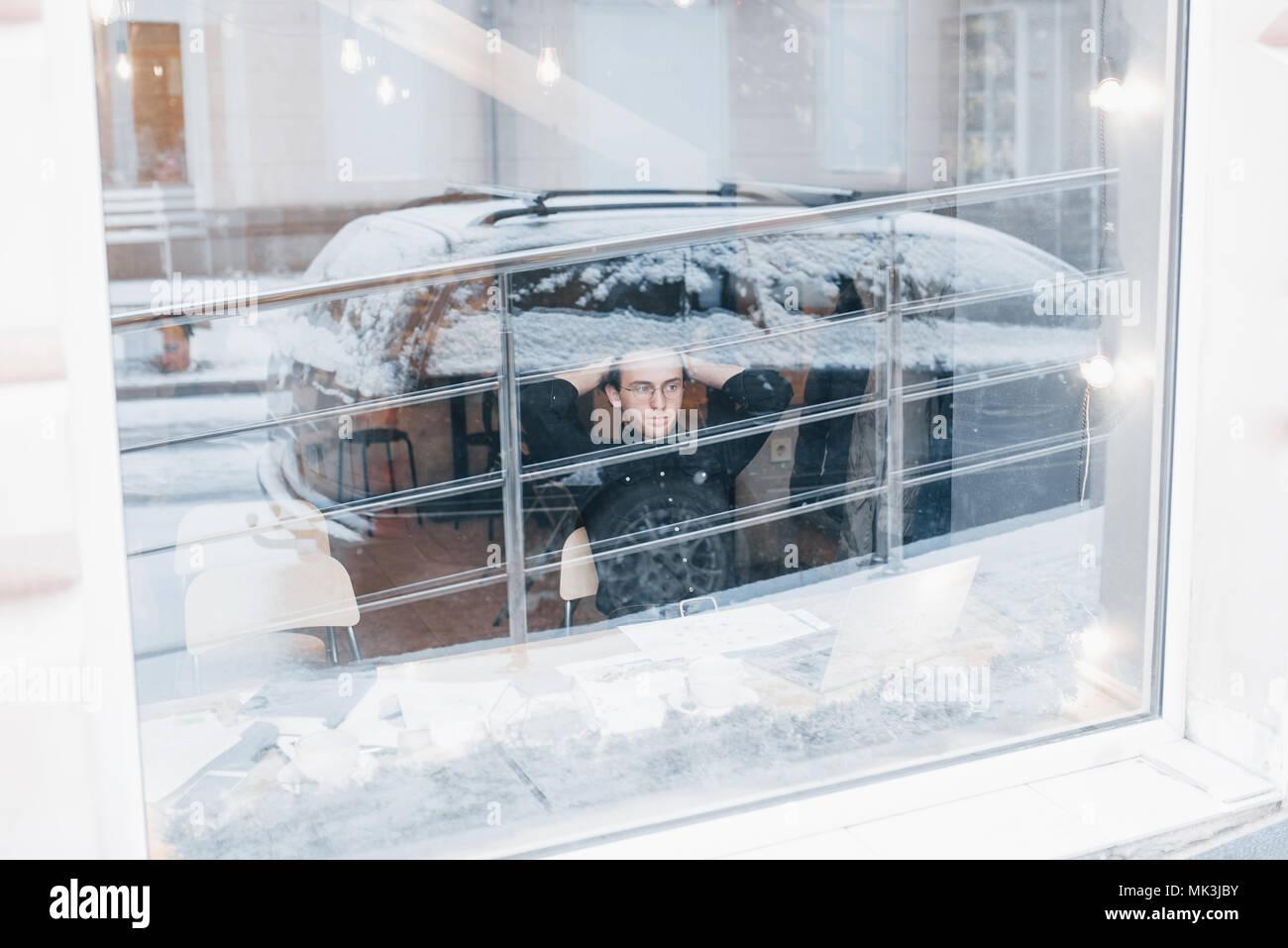 Jeune homme de boire du café en café en regardant par la fenêtre Photo Stock