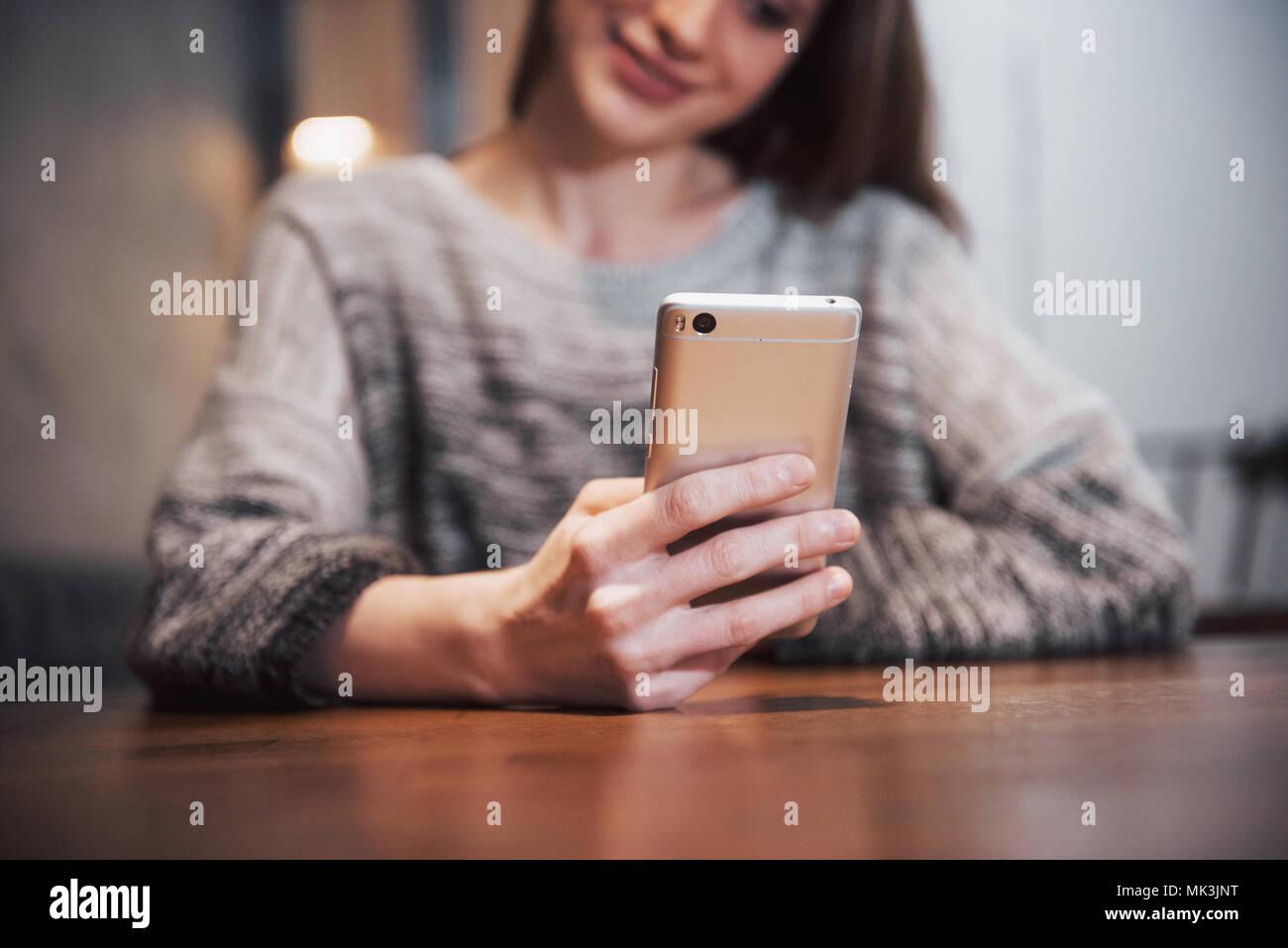 Une jolie fille avec de longs cheveux noirs s'interroge sur un nouveau projet durant une pause-café assis à une table dans un café Photo Stock