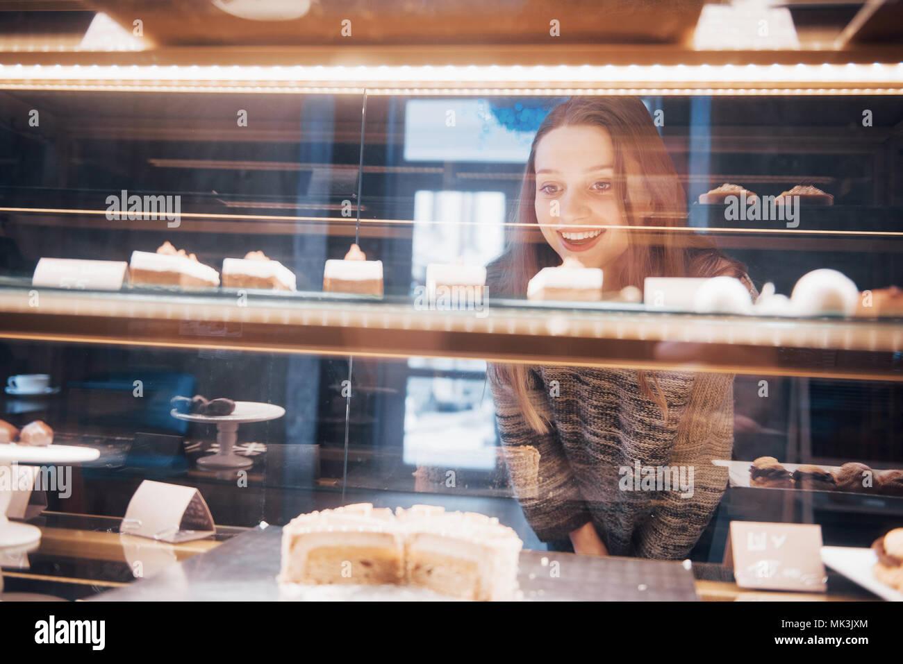 Smiling woman at caméra dans la vitrine avec de douces et des gâteaux dans l'intérieur moderne cafe Photo Stock