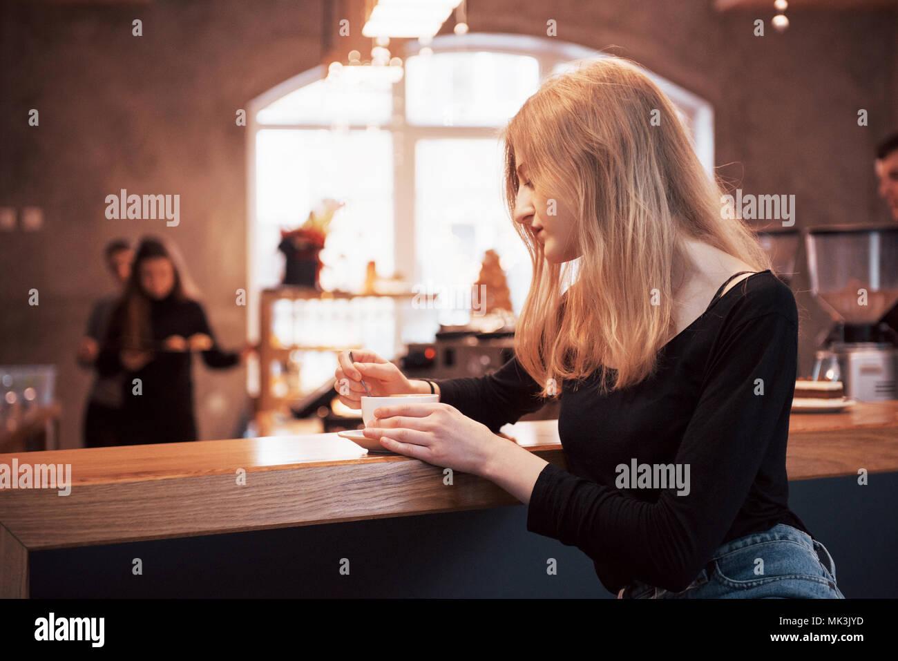 Smiling woman in cafe en utilisant des sms et téléphone mobile dans les réseaux sociaux, siégeant seul Photo Stock
