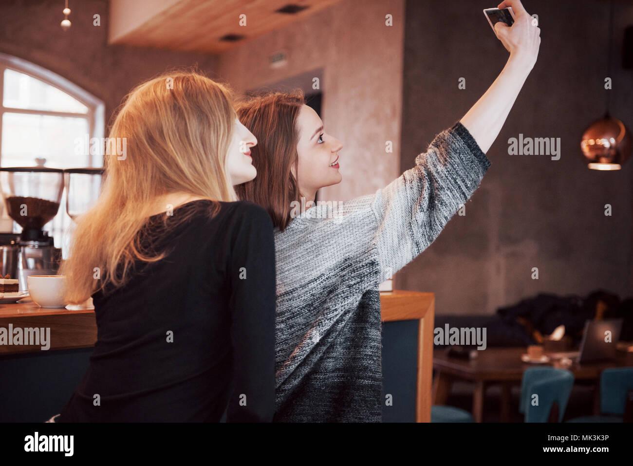 Deux amis de boire du café dans un café, en tenant vos autoportraits avec un téléphone intelligent et s'amuser faire des grimaces. Se concentrer sur la fille sur la gauche Banque D'Images