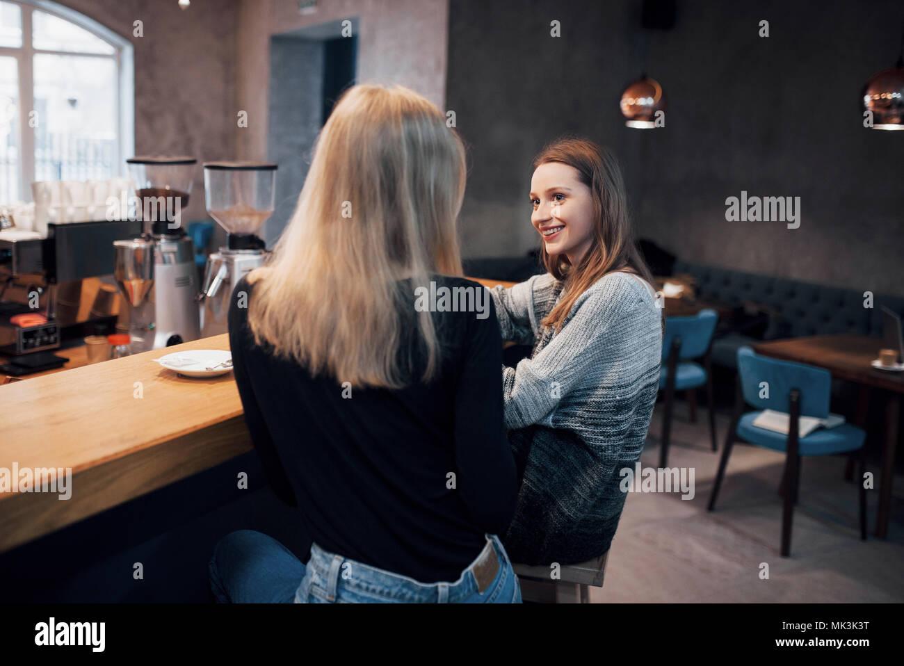 Deux amis appréciant café ensemble dans un café, assis à une table à discuter Photo Stock