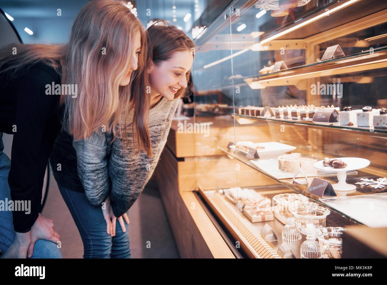 Deux heureux filles attirantes le choix de délicieux chocolats, ganaches et pralinés Photo Stock