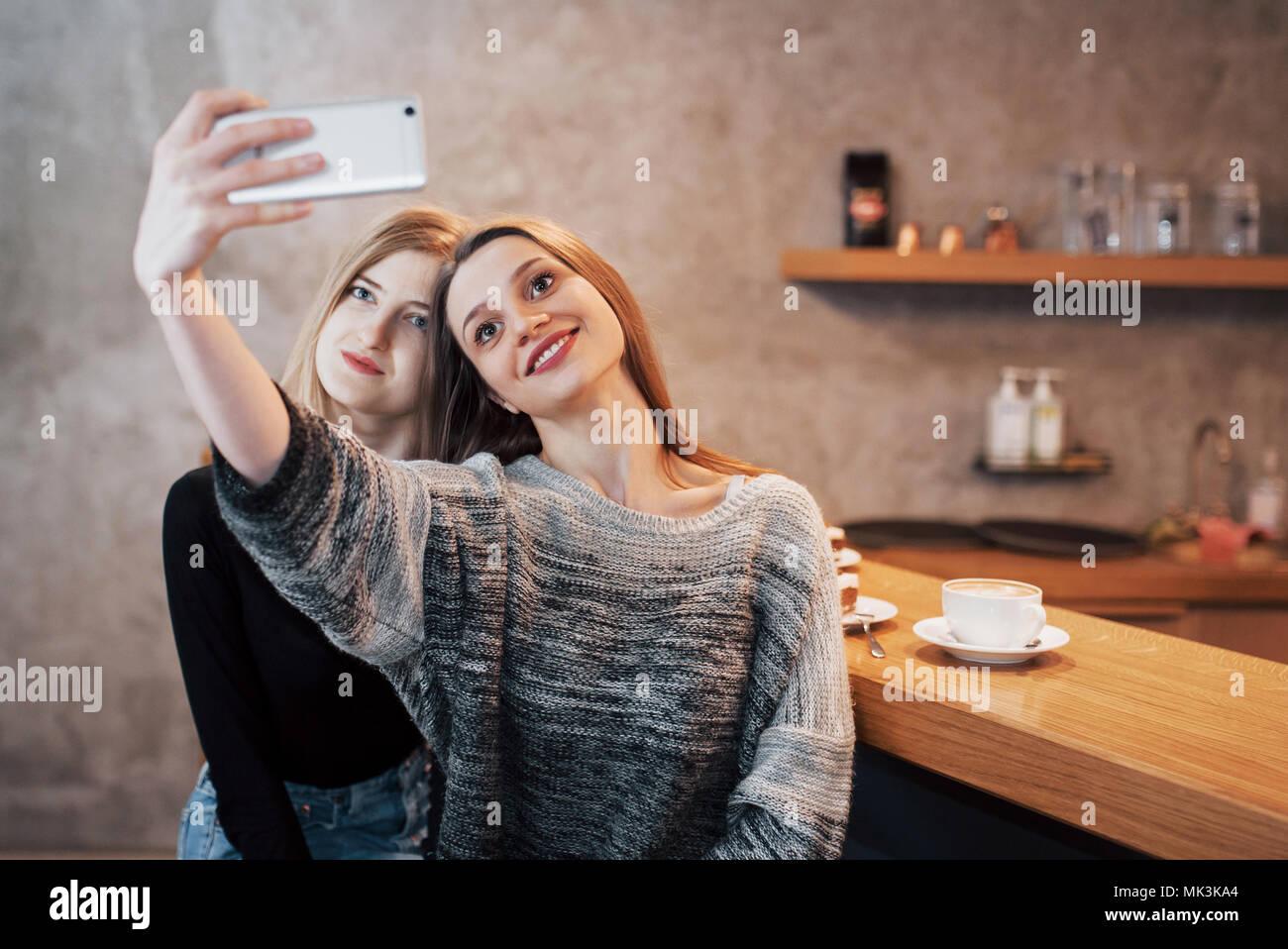 Deux femmes friends sitting in cafe selfies et faire Photo Stock