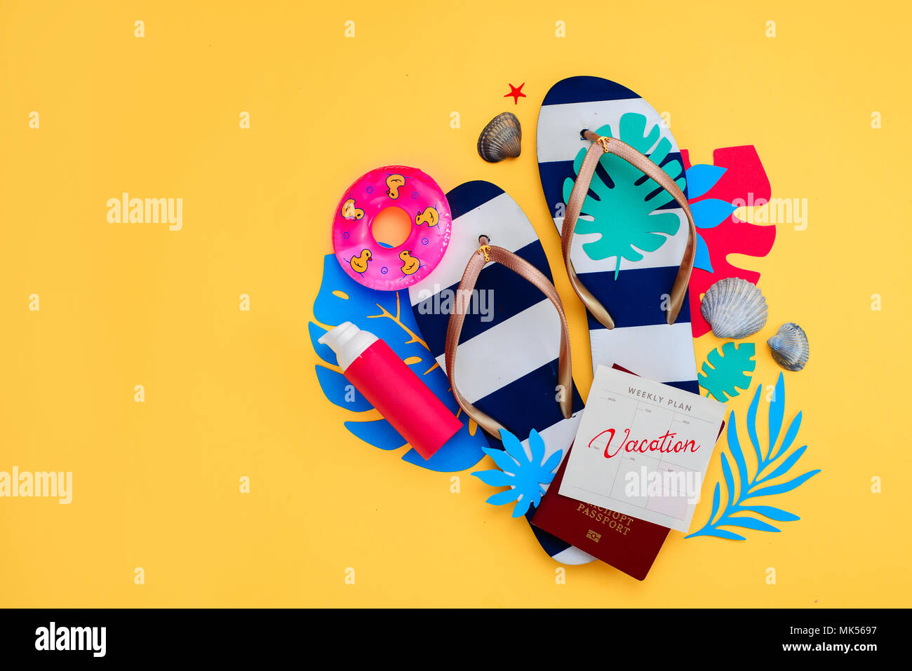 Concept des vacances, voyages et accessoires de plage avec copie espace. Tongs, feuilles tropicales et un calendrier avec locations de note sur un fond jaune. Photo Stock