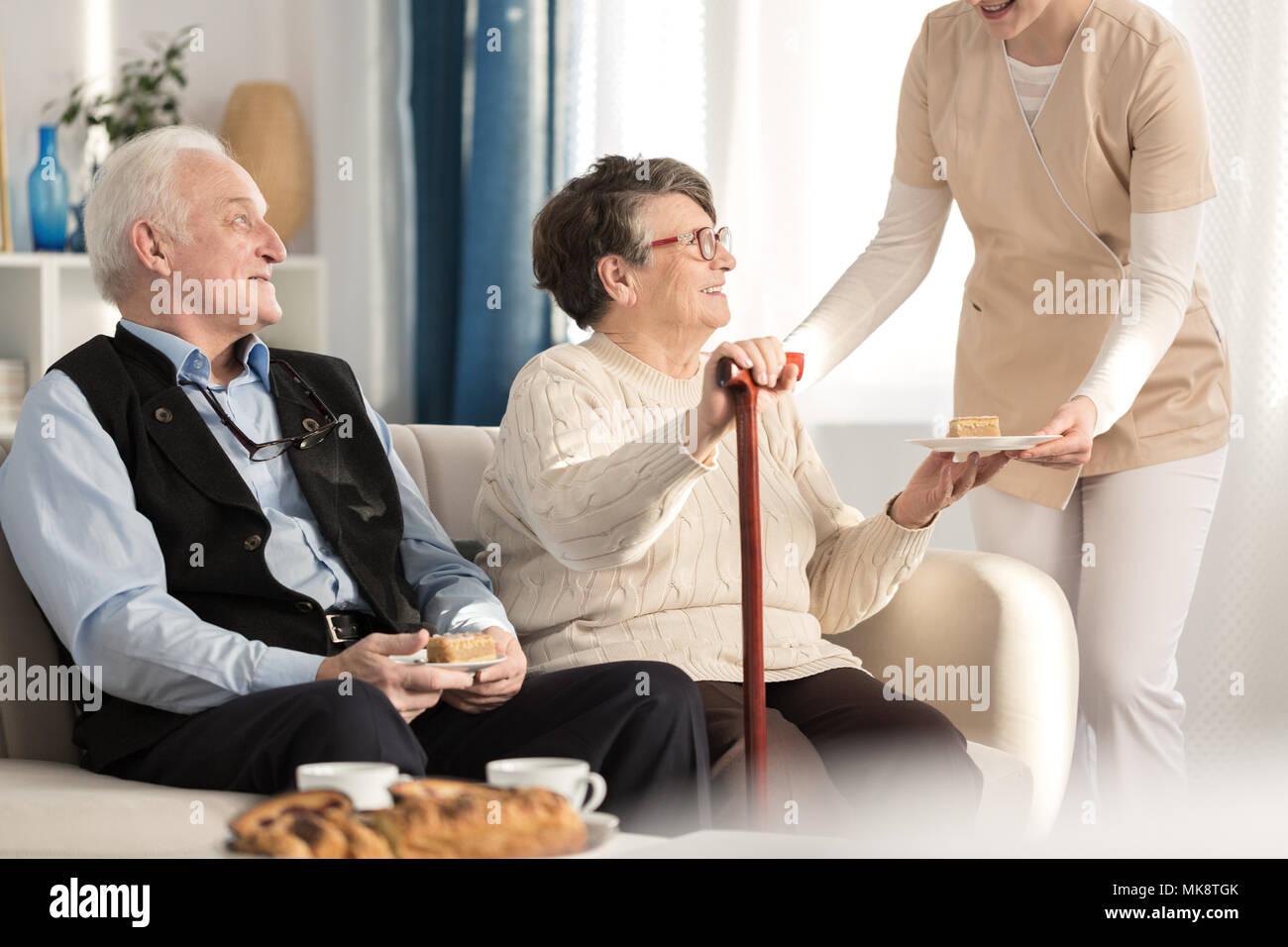 Couple gériatrique à l'arthrite assis sur une table et d'être servi un morceau de gâteau dans l'attente d'un rendez-vous chez le médecin lors d'une luxueuse salle de clini Banque D'Images