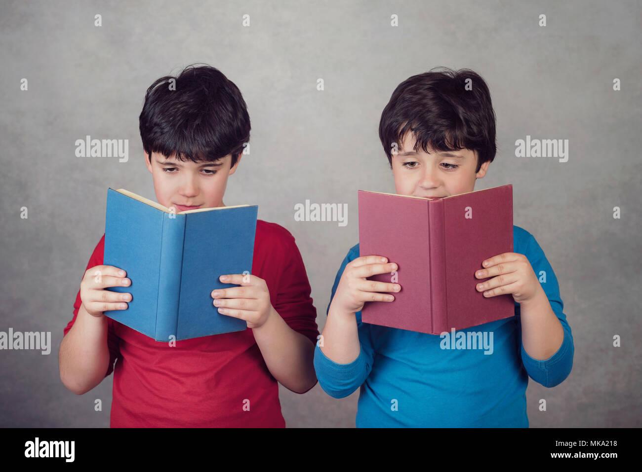 Enfants lisant un livre sur fond gris Photo Stock