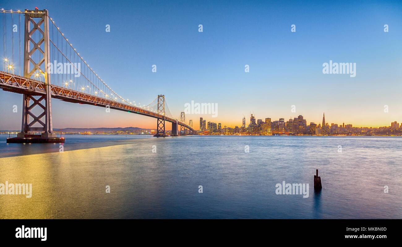 Classic vue panoramique de San Francisco skyline avec célèbre Oakland Bay Bridge illuminée en magnifique lumière du soir au coucher du soleil en été Photo Stock