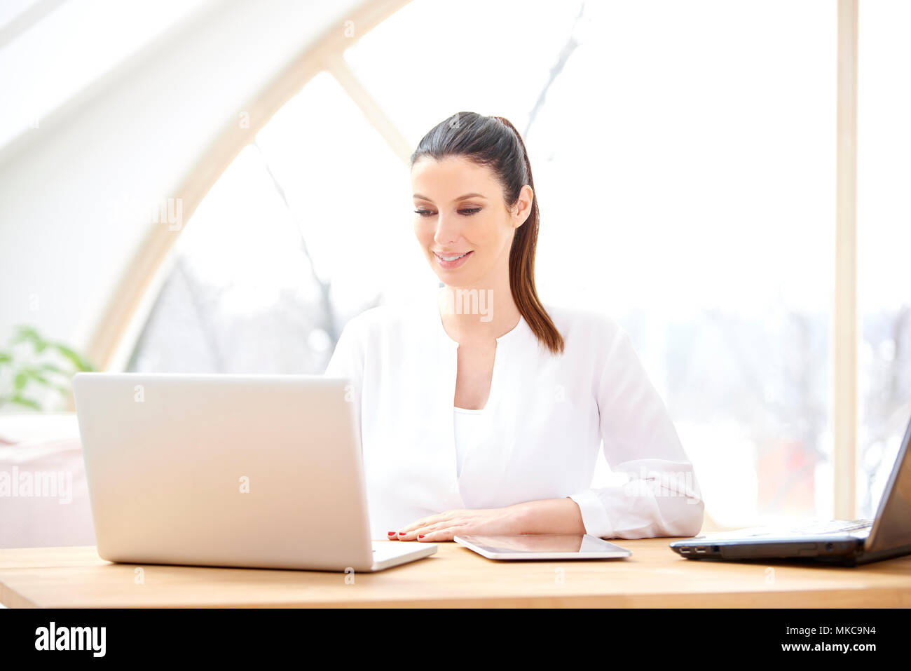 Belle jeune businesswoman working on laptop. Bureau à domicile. Photo Stock