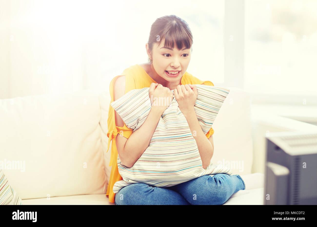 Jeune femme asiatique regardant la TV à la maison Photo Stock