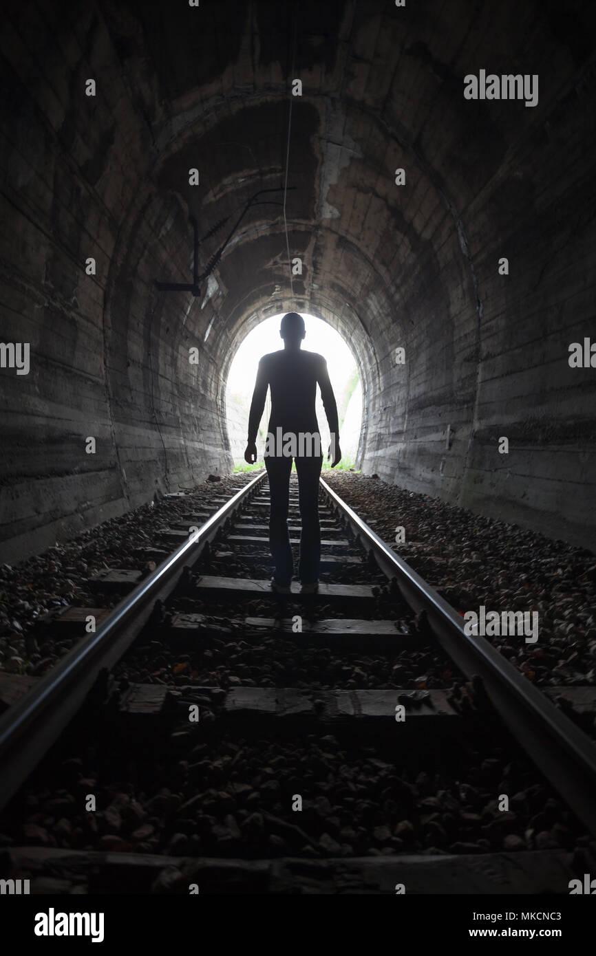 L'homme qui se profile dans un tunnel debout au milieu de la voie ferrée à la recherche vers la lumière au bout du tunnel dans une image conceptuelle Photo Stock