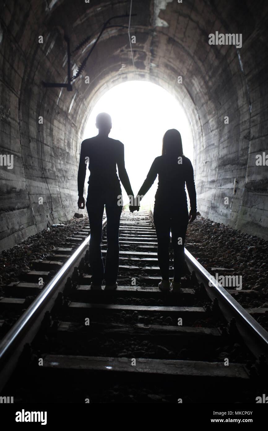 Couple marche main dans la main le long de la voie par un tunnel ferroviaire en direction de la lumière vive à l'autre extrémité, ils apparaissent comme des silhouettes contre le Photo Stock