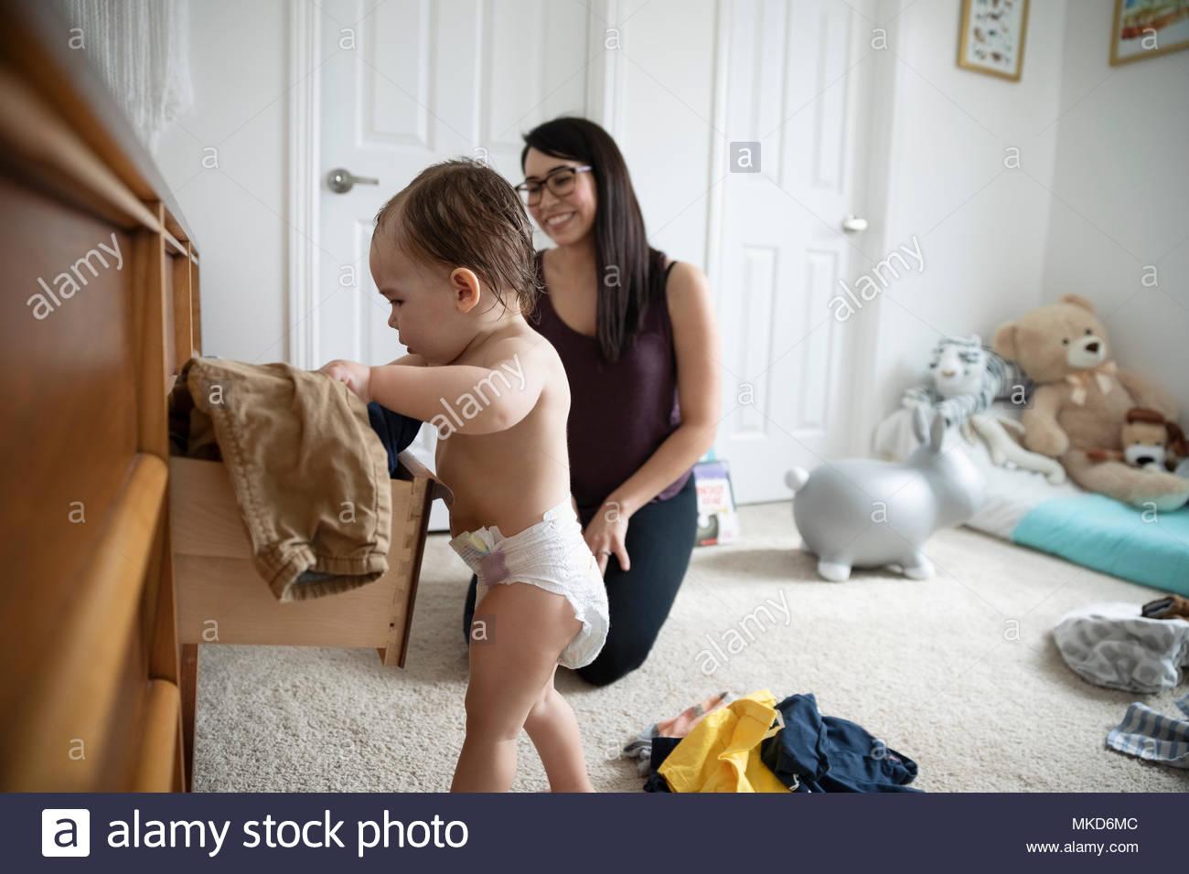 Mère regardant bébé curieux fils à dresser en pépinière Photo Stock