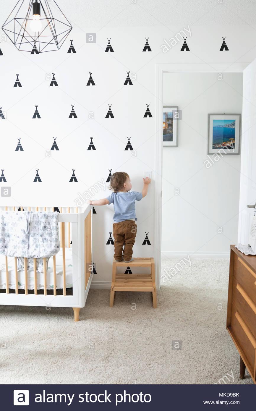 Mignon bébé garçon sur l'escabeau pour atteindre l'interrupteur d'éclairage en pépinière Photo Stock