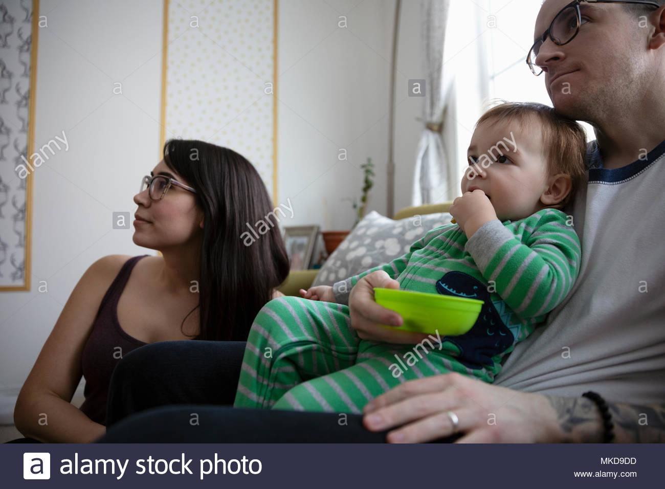 Jeune famille de manger, de regarder la télévision Photo Stock