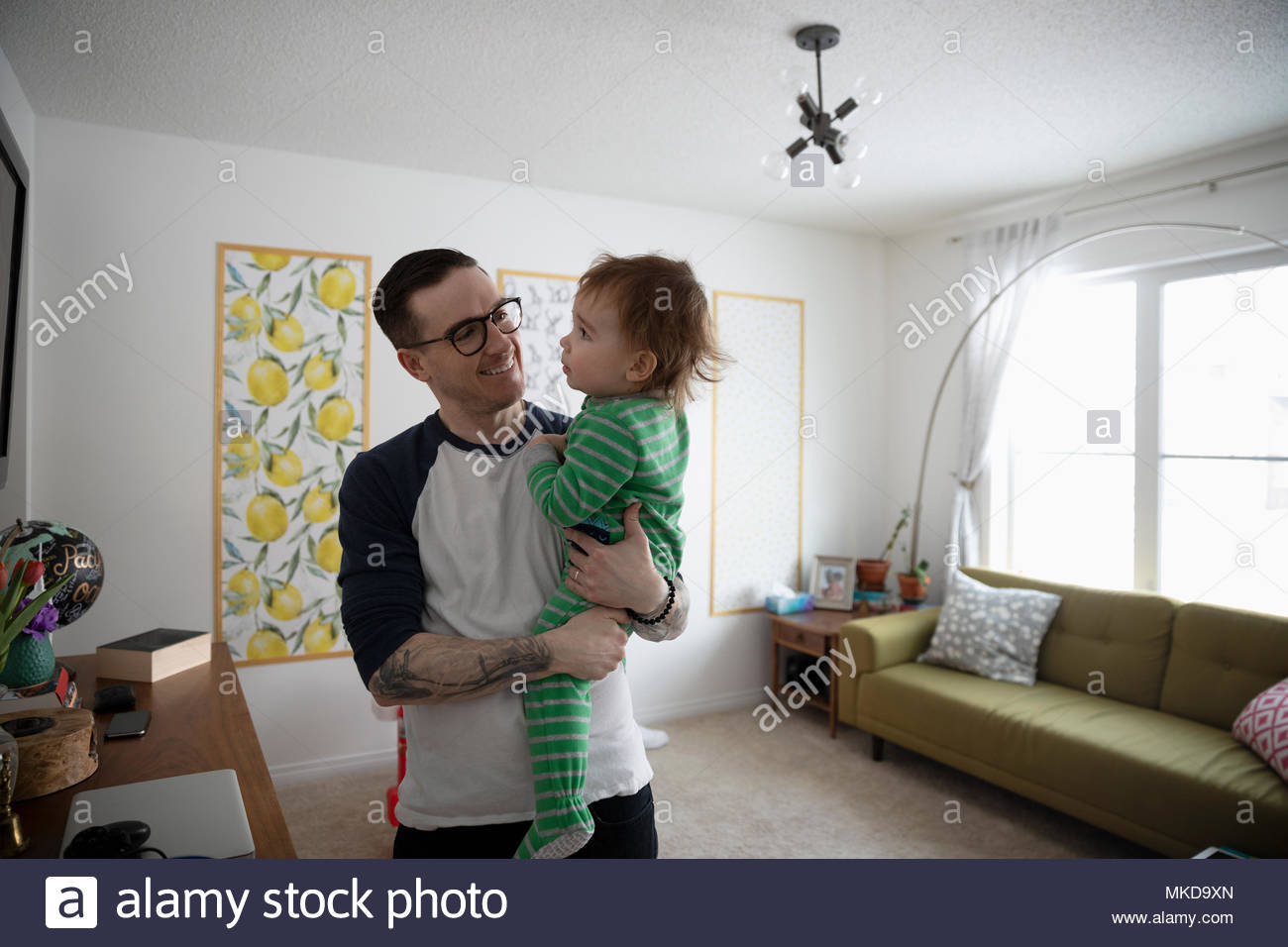 Père holding baby son in living room Photo Stock