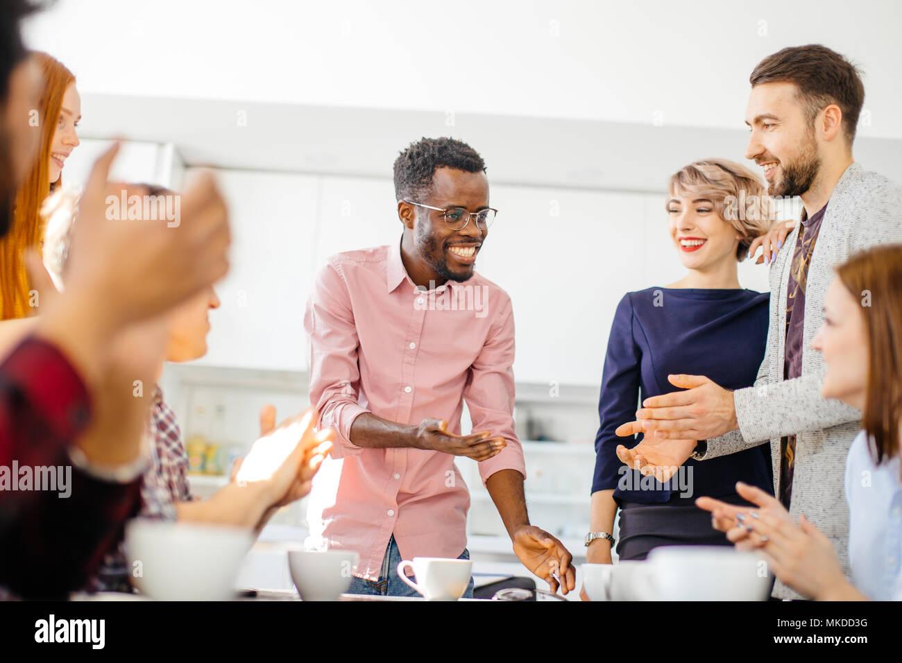 Leadered par membre du personnel de l'élégant homme africain est d'avoir une conversation agréable dans la cuisine à l'intérieur moderne Photo Stock