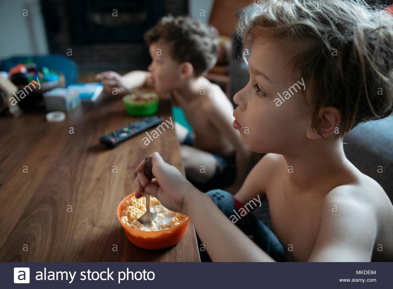 Curieux torse nu frères manger des céréales et de regarder la télévision Photo Stock