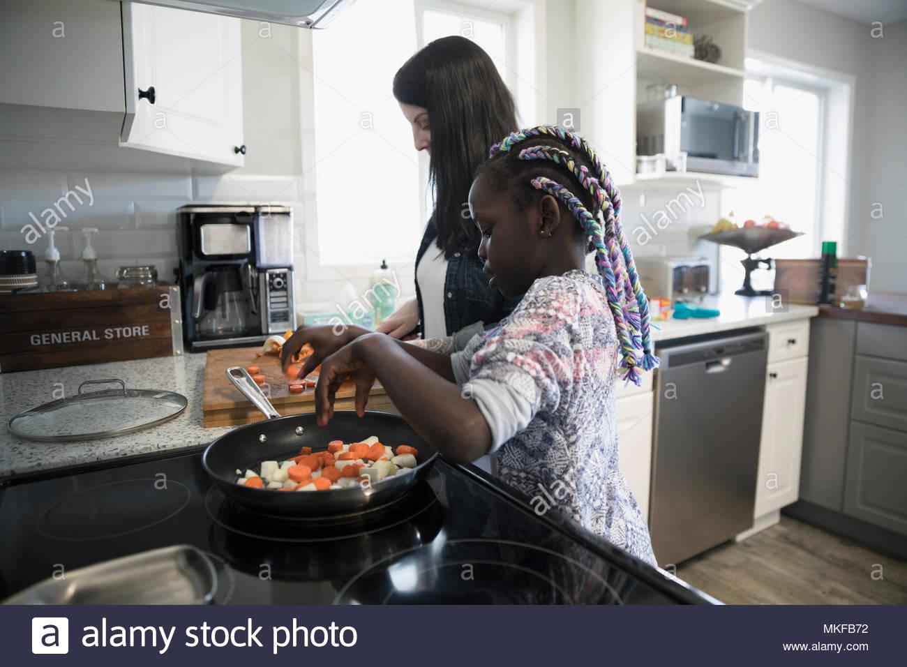 Mère et fille la préparation et la cuisson des légumes à la cuisine cuisinière Photo Stock