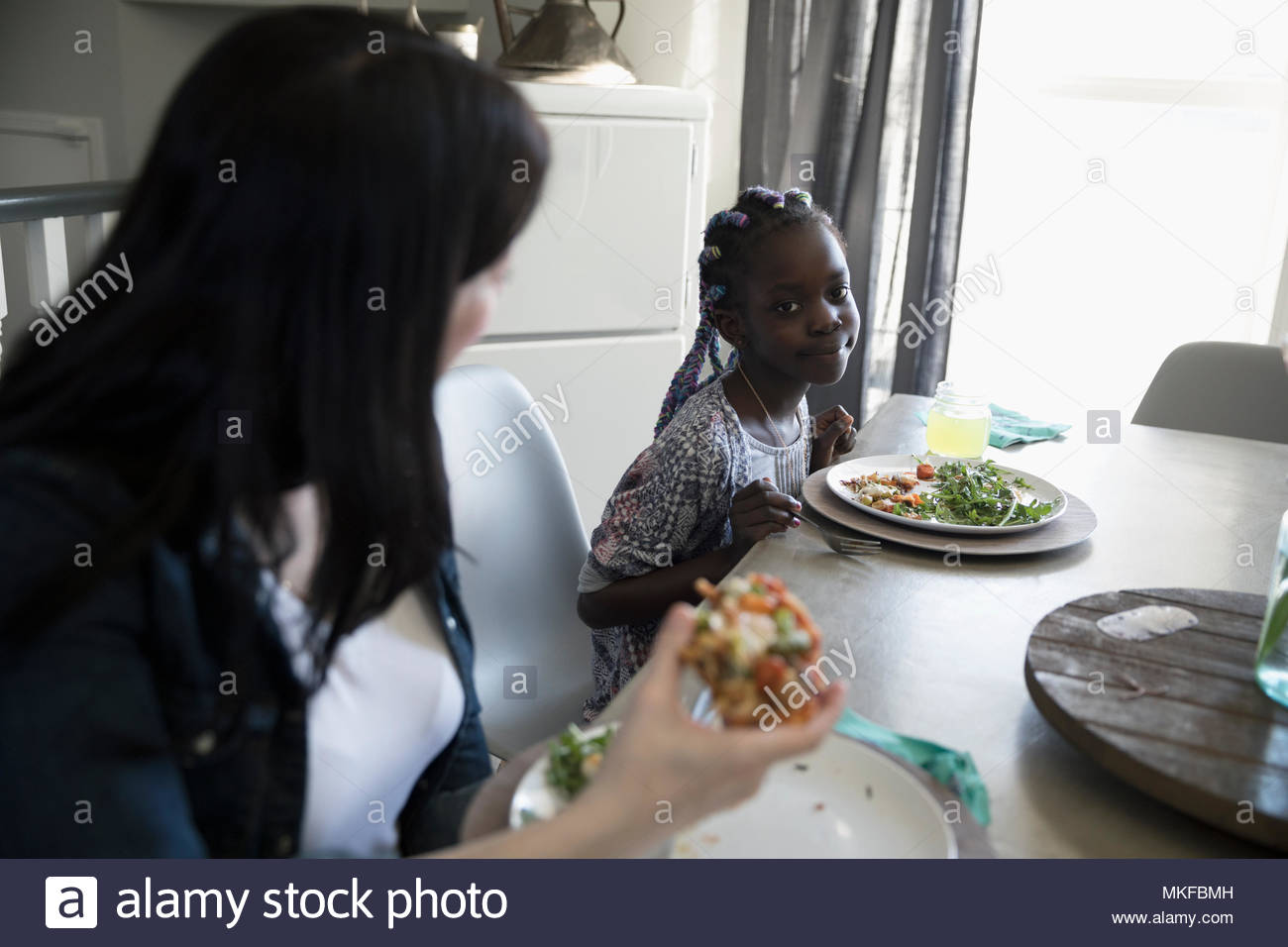 Mère et fille de manger des pizzas et salade à table à manger Photo Stock