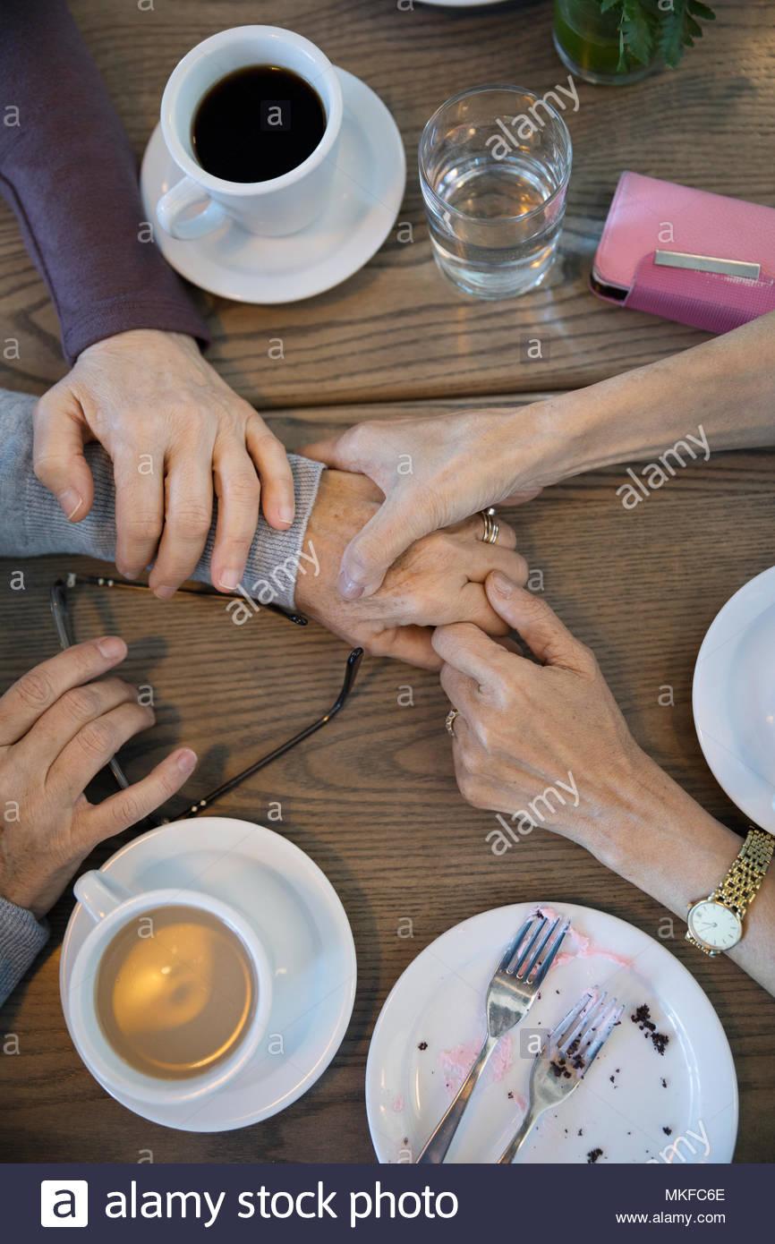 Vue de dessus les femmes tenant les mains, ami réconfortant dans cafe Photo Stock