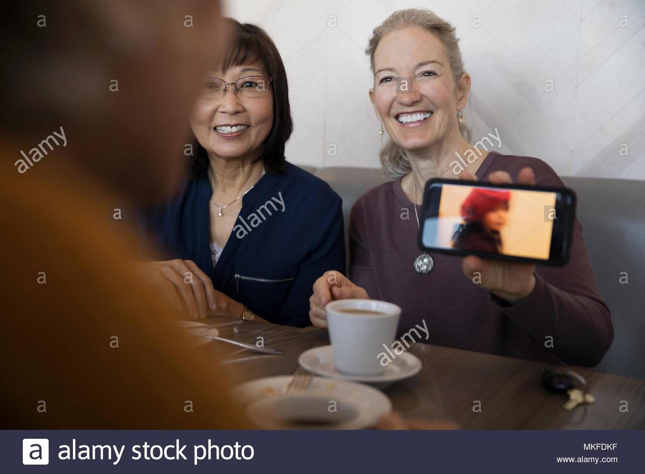 Fier senior woman with camera phone montrant photo de petite-fille à des amis Photo Stock