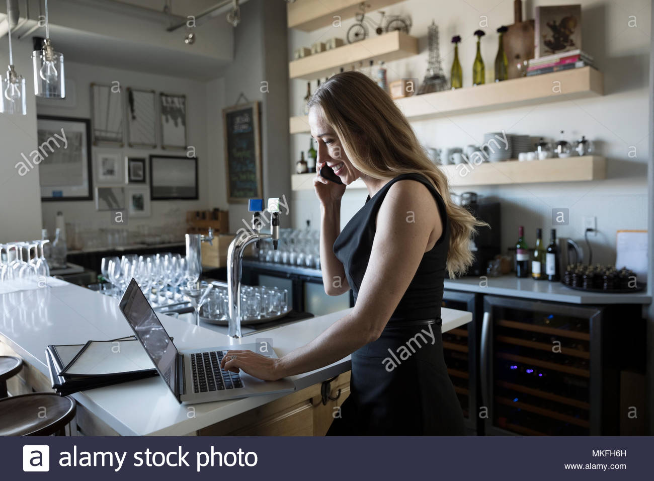 Femme small business owner téléphone intelligent et working at laptop in cafe Photo Stock
