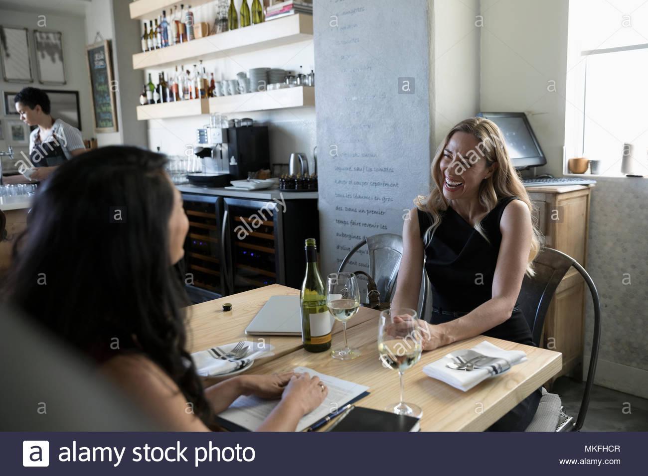 Businesswomen talking, profitant du vin au déjeuner de travail à cafe Photo Stock