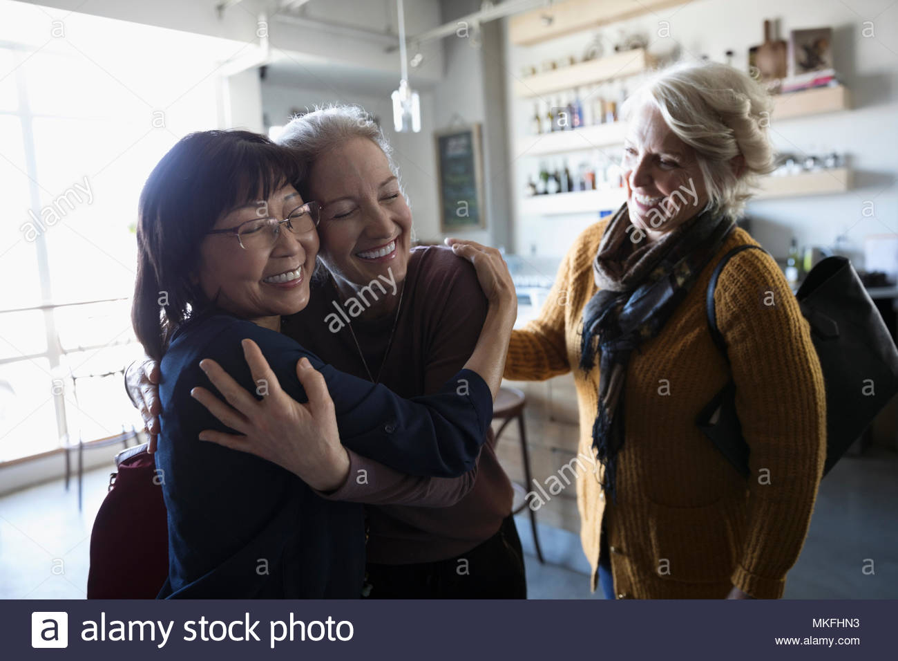 Happy senior women friends accueil, hugging in cafe Photo Stock