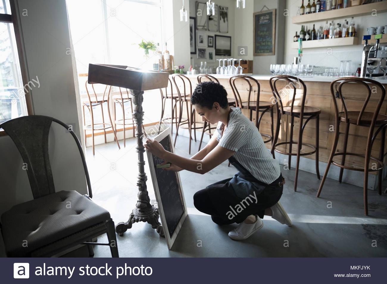 Jeune femme propriétaire de petite entreprise la préparation de menu sur cafe tableau noir Photo Stock
