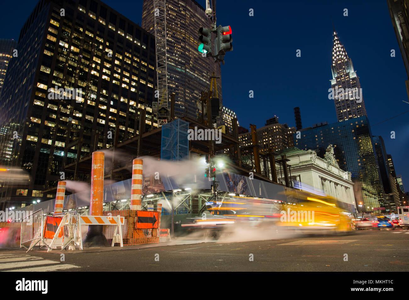 NEW YORK - Etats-Unis - 31 octobre 2017 - Une longue exposition photo de voitures traversant une intersection à New York pendant que la vapeur qui sort du trou. Banque D'Images