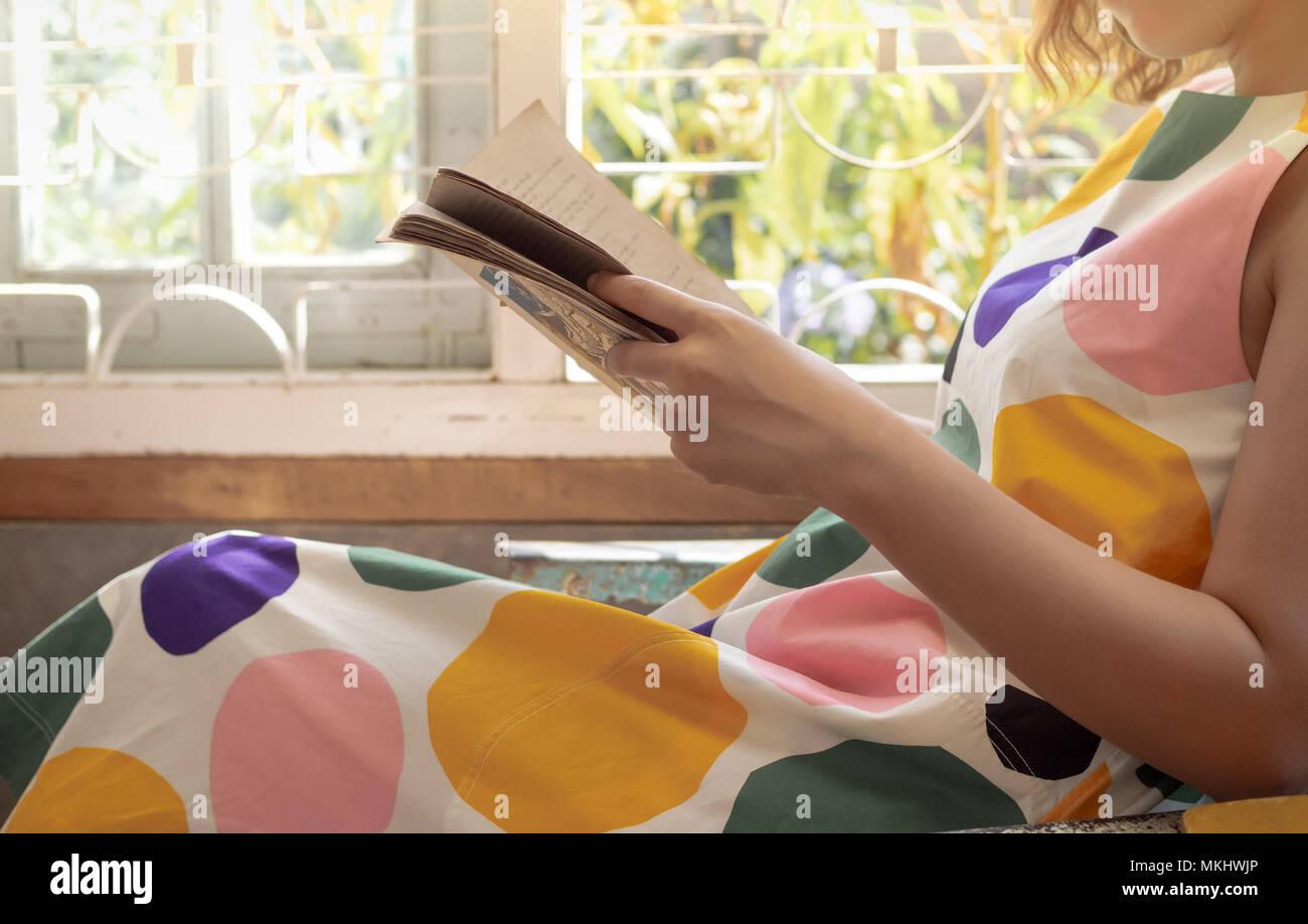 Femme en robe colorée aime lire le livre de poche près de la fenêtre sur Sunshine Day, le livre dans ses mains Photo Stock