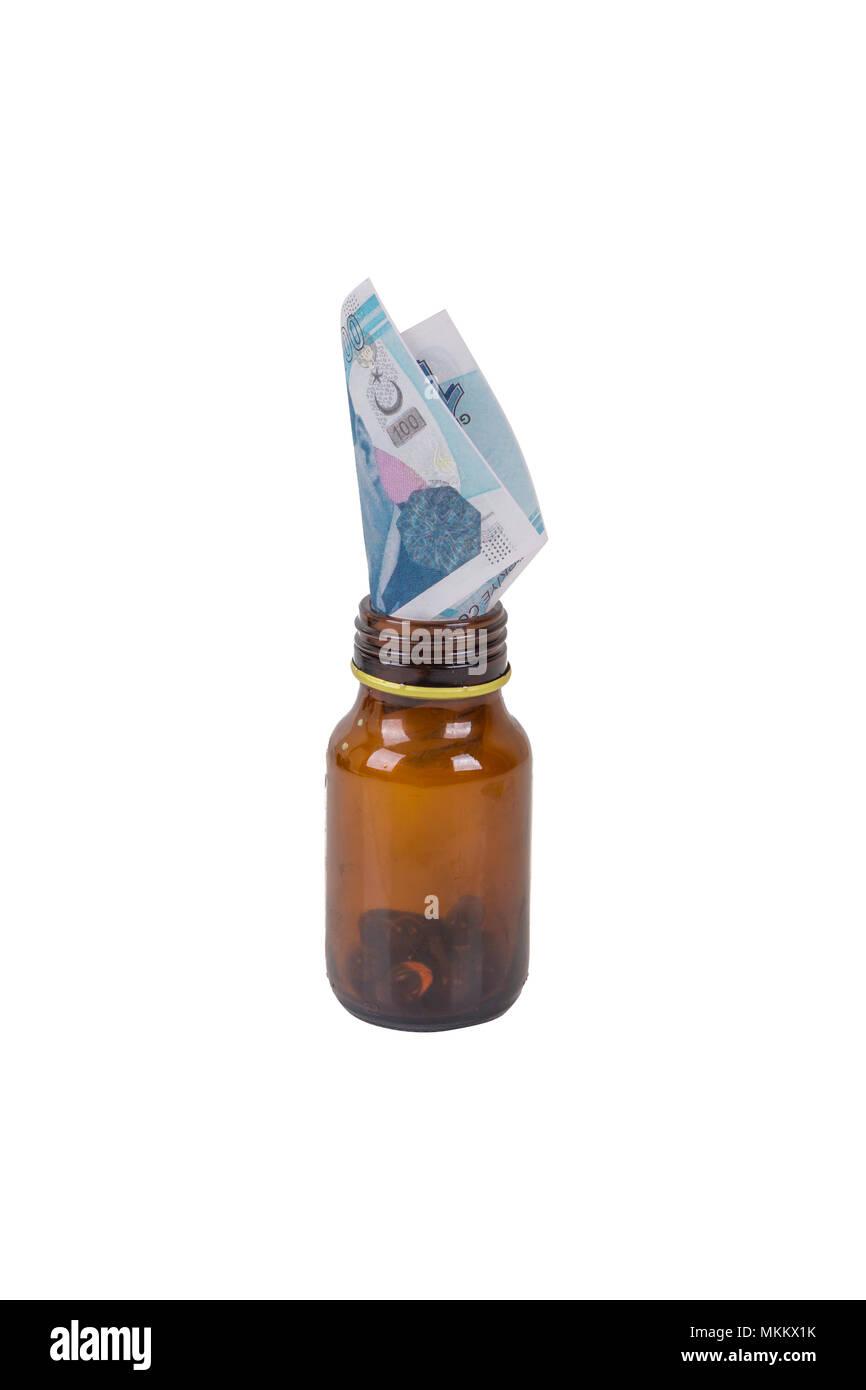 Pile de livres turques à l'intérieur de billets et de médicaments comprimés bouteille avec la signification de la santé et de la médecine, expensiveness isolé sur fond blanc. Photo Stock