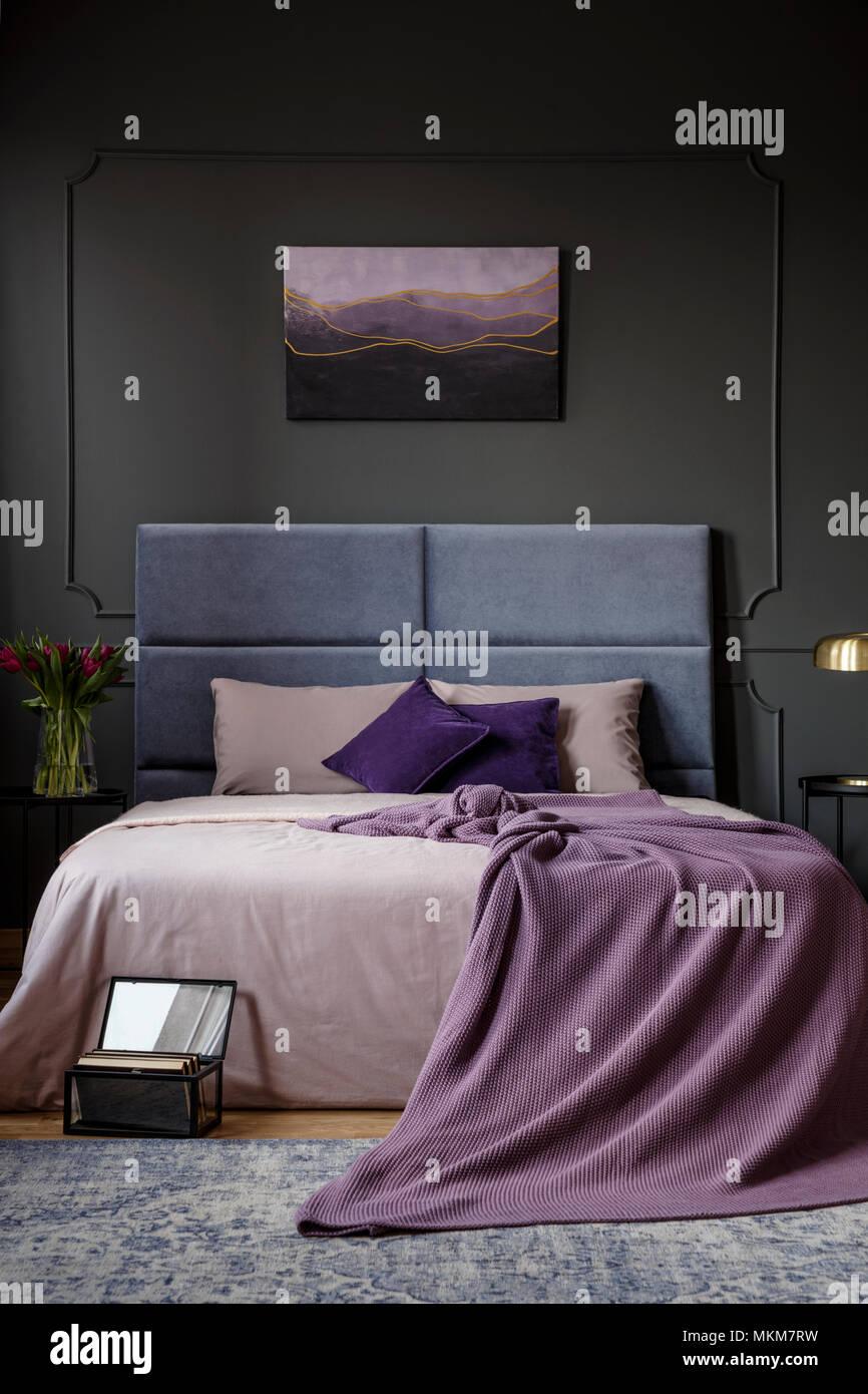 couverture pourpre sur le lit dans une chambre sombre intérieur avec