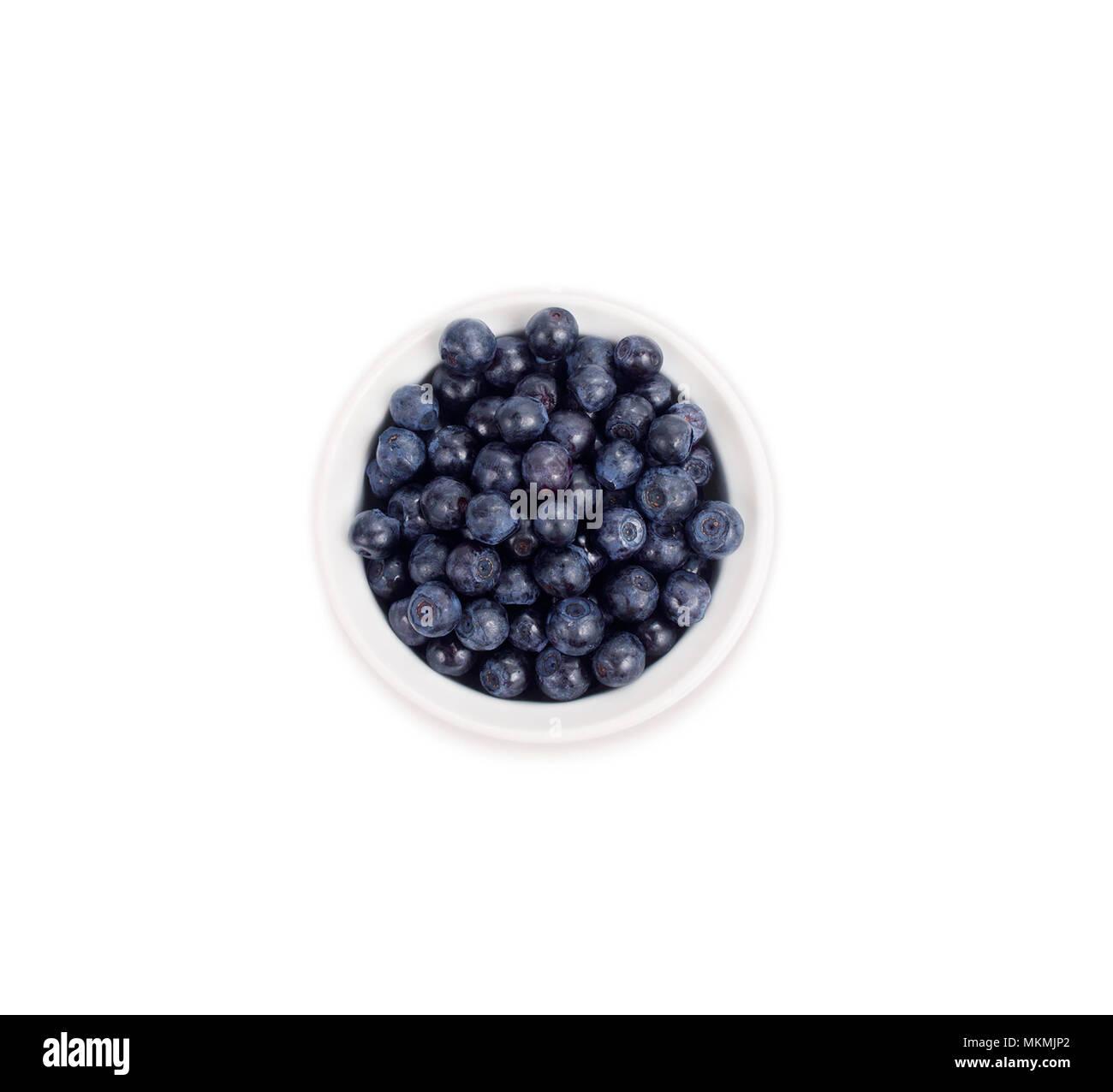 Les myrtilles dans un boin en bois un bol en céramique blanche. Vue d'en haut. Mûr et savoureux bleuets isolé sur fond blanc. Banque D'Images