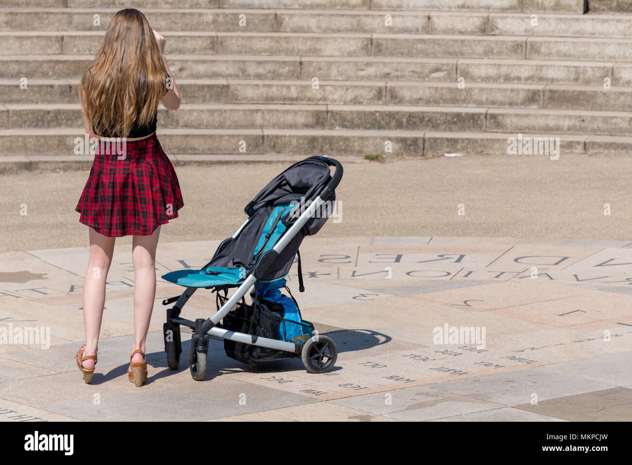 Jeune mère en jupe tartan rouge et talons hauts avec blue poussette en  amphithéâtre pierre dff5e596fc83