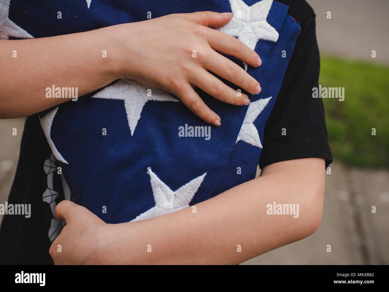 Un jeune garçon tenant un drapeau américain pliée. Photo Stock