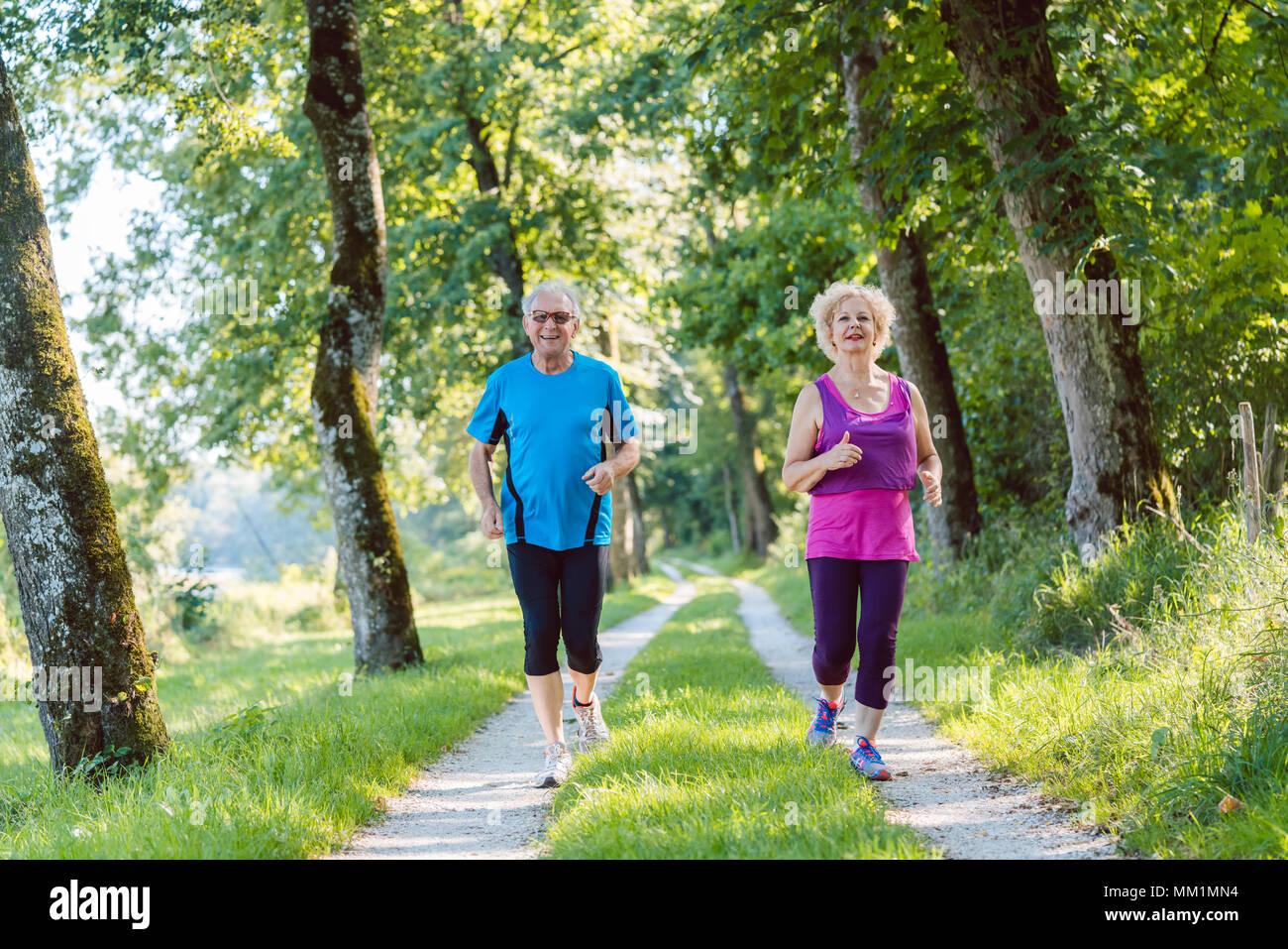 Deux aînés avec un style de vie sain tout en souriant ensemble jogging Photo Stock
