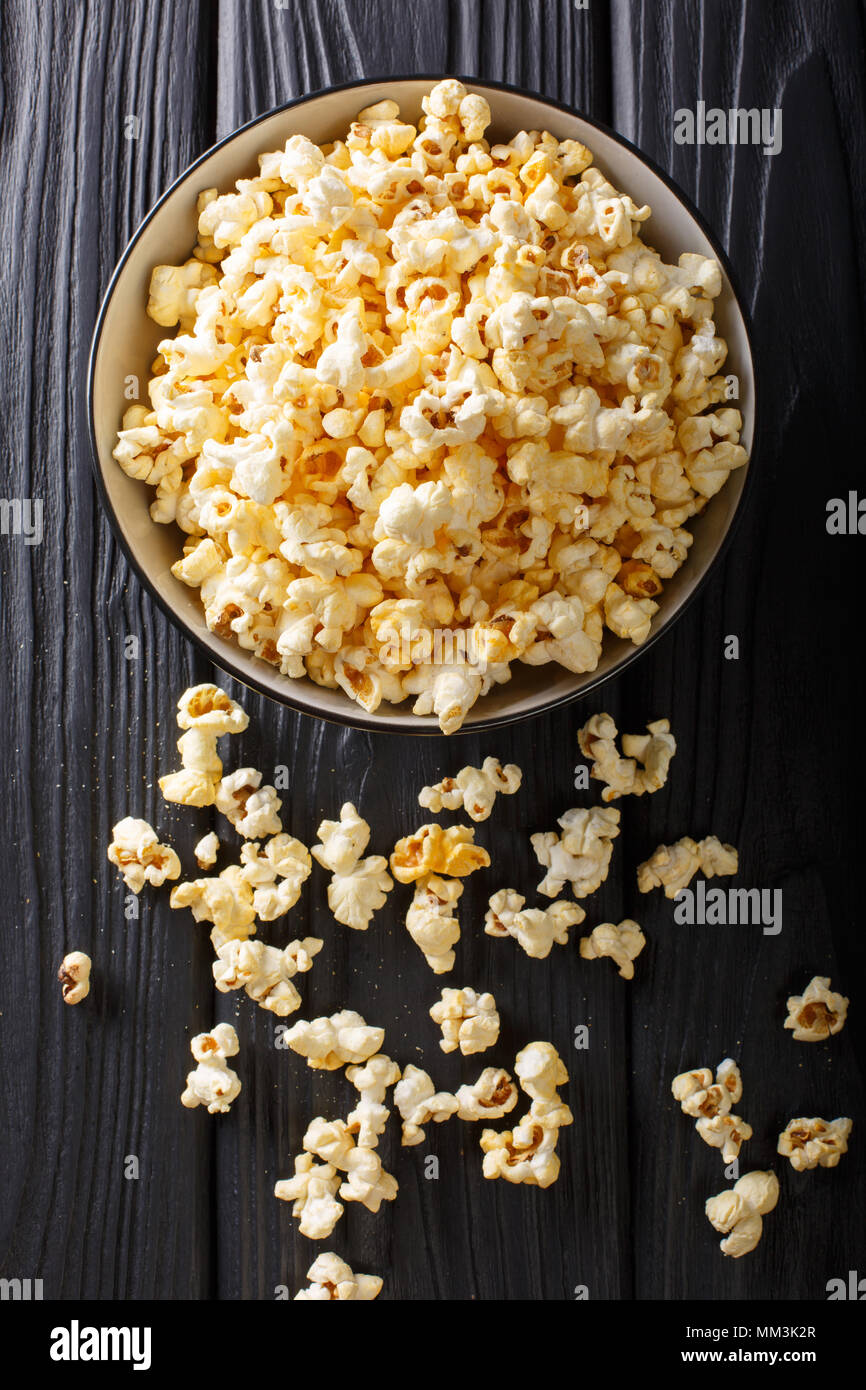 Le maïs soufflé de fromage dans un bol, gros plan sur une table. Haut Vertical Vue de dessus Photo Stock