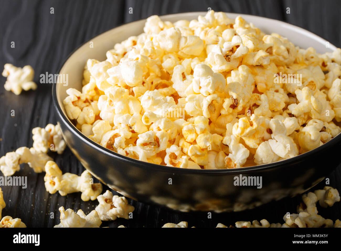 Snack populaire: popcorn salé avec le fromage cheddar et le parmesan dans un bol sur la table horizontale. Photo Stock