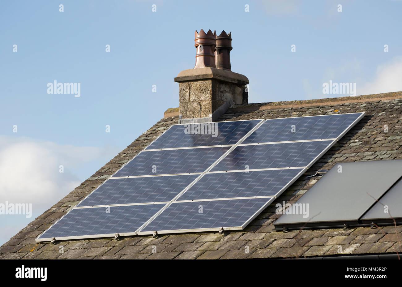Des panneaux solaires sur le toit d'une maison à côté des pots de cheminée traditionnelle. Nord du Dorset England UK Photo Stock