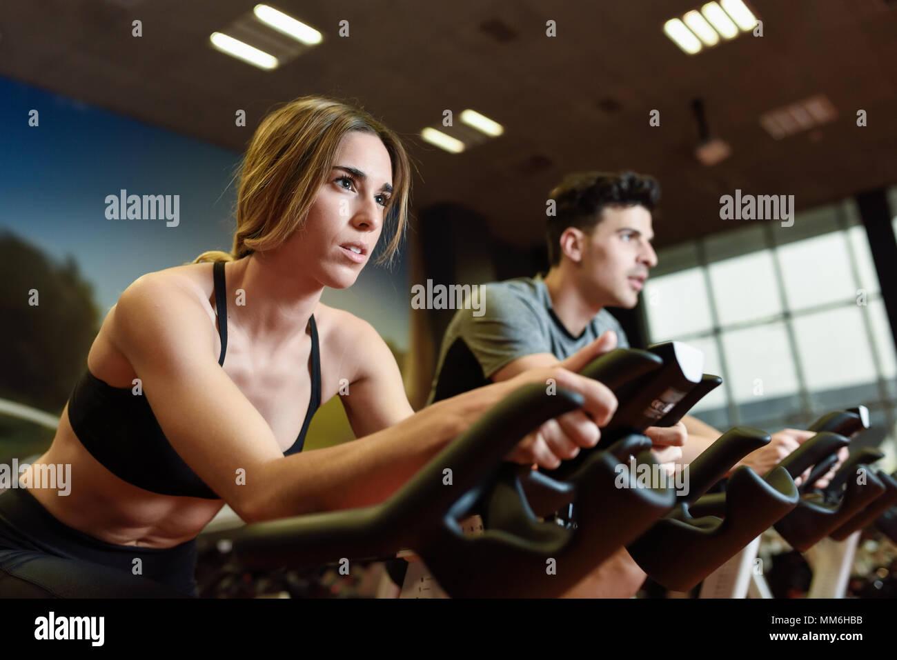 Jolie femme et l'homme autour de la salle de sport, l'exercice de jambes faisant cardio vélo vélos. Dans un couple de spinning portant des vêtements de sport. Photo Stock