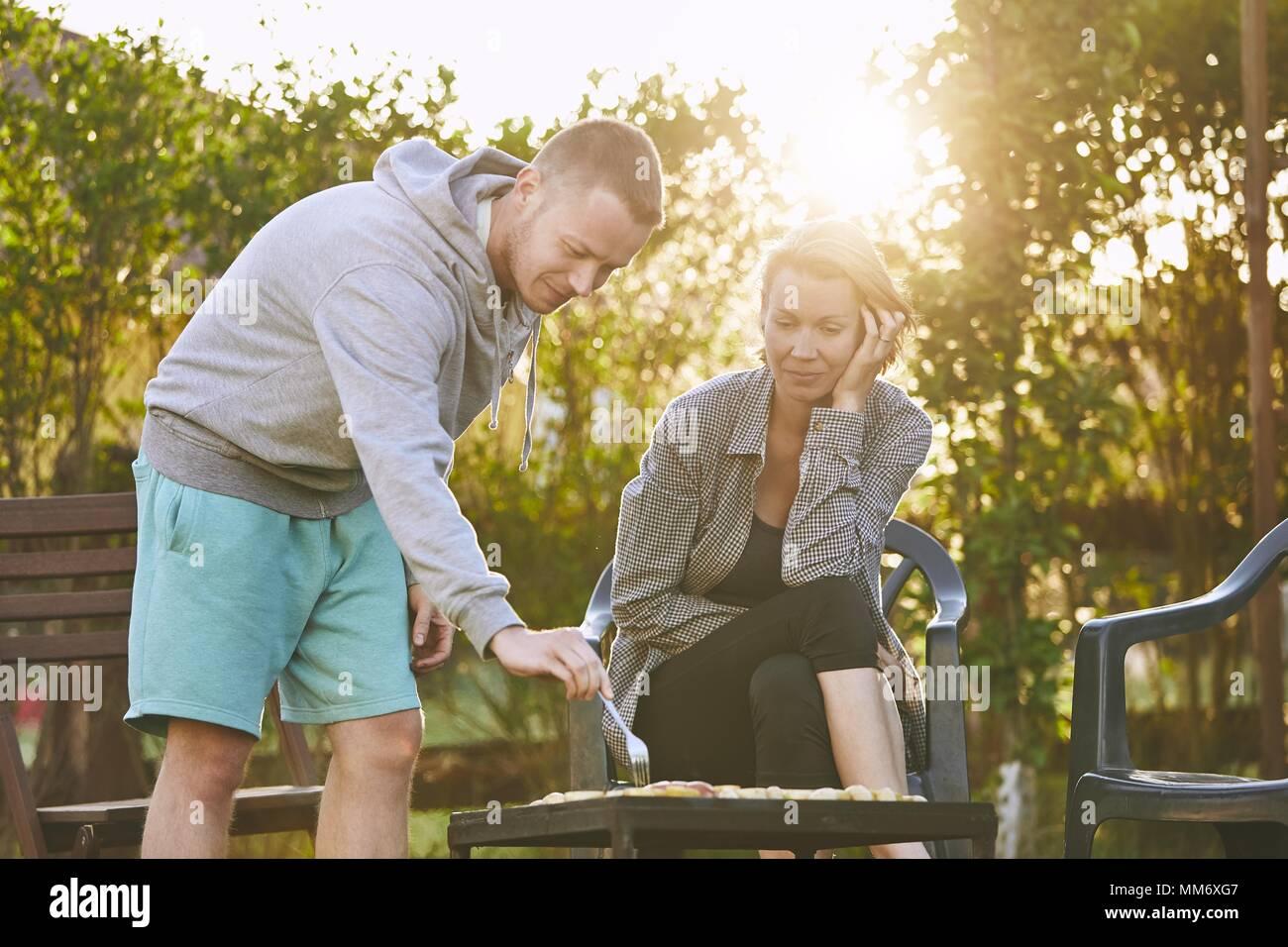 L'été sur le jardin. Jeune couple barbecuing contre chalet au coucher du soleil. Photo Stock